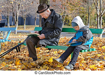 Young boy reading with his grandfather - Young boy reading...