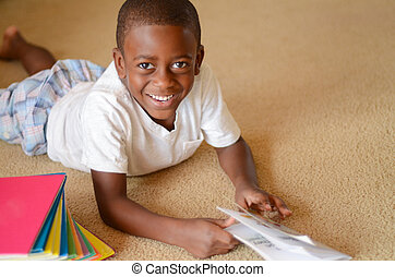 Early Reading - A young African American boy laying on the...