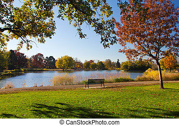 Park Bench by the Lake in Fall - Empty park bench by scenic...