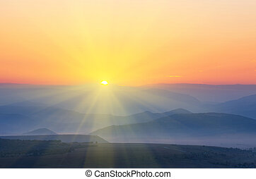 The sun with rays rises over the mountains. natural...