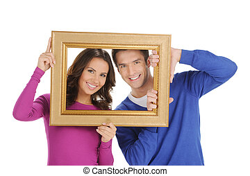 Couple in frame. Beautiful young couple looking through a picture frame and smiling while isolated on white
