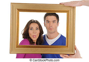 Funny people in frame. Beautiful young couple looking through a picture frame and grimacing while isolated on white