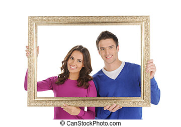 Happy couple in frame. Beautiful young couple looking through a picture frame and smiling while isolated on white