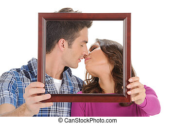 Kissing in a picture frame. Beautiful young couple holding a picture in front of their faces and kissing while isolated on white
