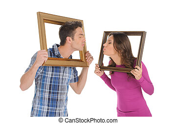 Couple with picture frames. Beautiful young couple holding a picture frames in their hands and trying to kiss each other while isolated on white