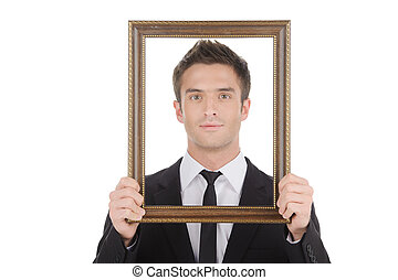 Businessman in picture frame. Handsome young man in formalwear looking through a picture frame while isolated on white
