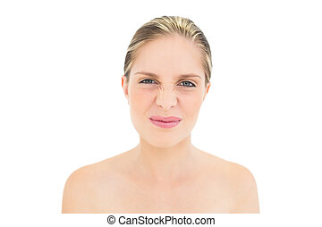 Funny fresh blonde woman wrinkling her nose on white...