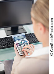 Over shoulder view of businesswoman using calculator in...