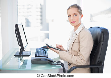 Side view of blonde businesswoman using calculator