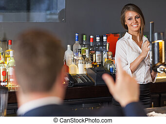 Handsome man ordering a drink from gorgeous waitress in a...