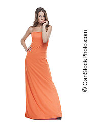 Beauty in dress. Beautiful young woman in orange dress posing while isolated on white