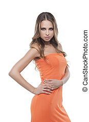 Beautiful young woman. Beautiful young woman in orange dress posing while isolated on white