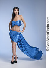Beauty in blue. Full length of attractive young black hair woman posing while isolated on coloured background