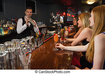Handsome bartender making cocktails for attractive women in...