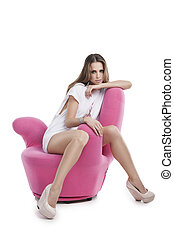 Beauty on chair. Attractive young woman sitting on the pink...