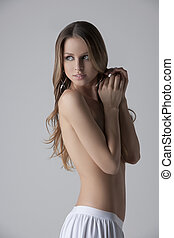 Naked beauty. Attractive young woman standing topless and covering breasts with hands while isolated on white