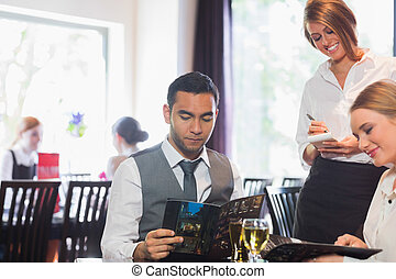 Two business people ordering dinner from waitress in...