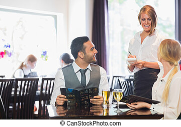 Business people ordering dinner - Smiling business people...