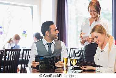 Business people reading menu and ordering in a restaurant