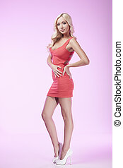 Beauty in red dress. Attractive blond hair woman posing while isolated on coloured background