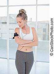 Relaxed sporty blonde wearing armband holding mp3 player -...
