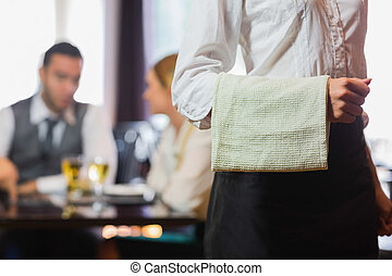 Waitress standing in front of two business people talking