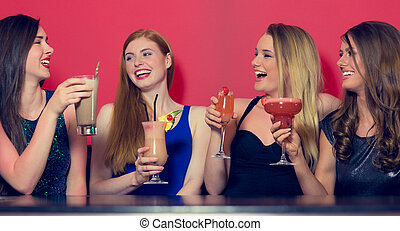 Attractive friends clubbing holding cocktails and chatting...
