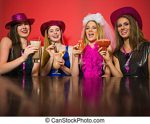Laughing friends having hen party holding cocktails looking...