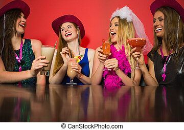 Laughing friends at a hen night drinking cocktails and...