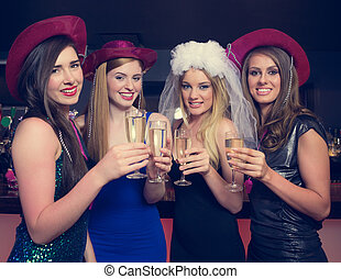 Attractive friends clinking champagne glasses at hen night...