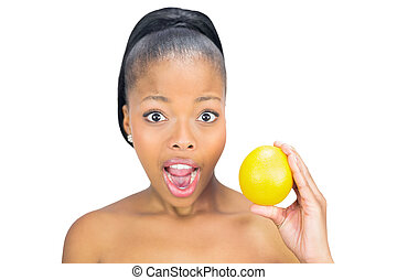 Surprised woman holding orange against white background