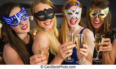 Smiling friends holding champagne glasses wearing masks...