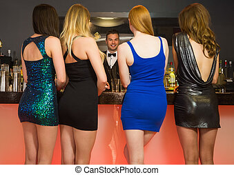 Attractive friends ordering drinks from barkeeper at...