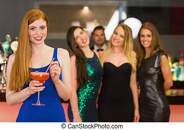 Attractive woman holding cocktail standing in front of her...