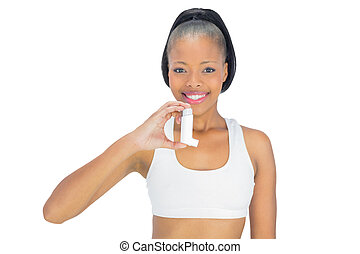 Smiling woman holding asthma inhaler while looking at camera