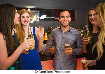 Happy friends holding beers and chatting in the nightclub