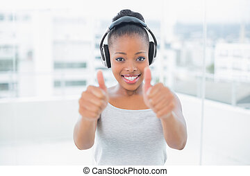 Happy woman listening to music with headphones and giving thumbs up while looking at camera