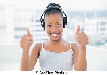 Smiling woman listening to music with headphones and giving thumbs up while looking at camera