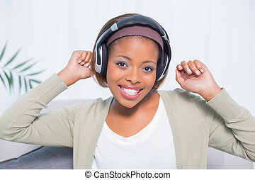 Dancing woman listening to music with headphones while looking at camera in her living room