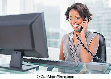 Smiling businesswoman talking on phone while looking at...