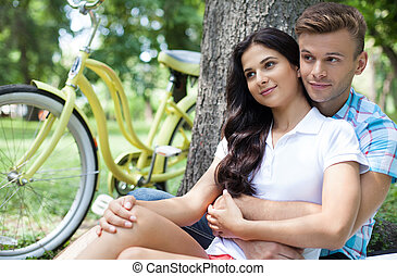 Couple in park. Cheerful young couple sitting close to each other and leaning at the tree