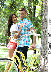 Loving couple with bike. Cheerful young loving couple standing close to each other and leaning at the bike