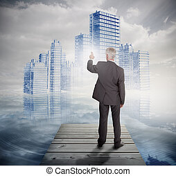 Rear view of mature businessman touching holographic city...