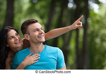 Couple having fun in park. Young loving couple having gun at...
