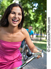 Bike ride at park. Cheerful young couple riding bikes in park