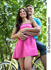 Couple on bicycle. Beautiful young loving couple standing near bicycle and hugging