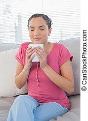 Woman on the sofa enjoying a coffee