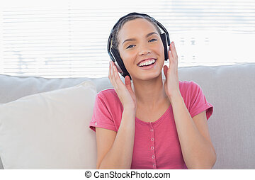 Happy woman sitting on sofa with headphones on and listening...