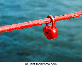red padlock in the form of heart on fence