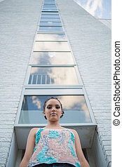 Attractive woman standing in front of a tall building